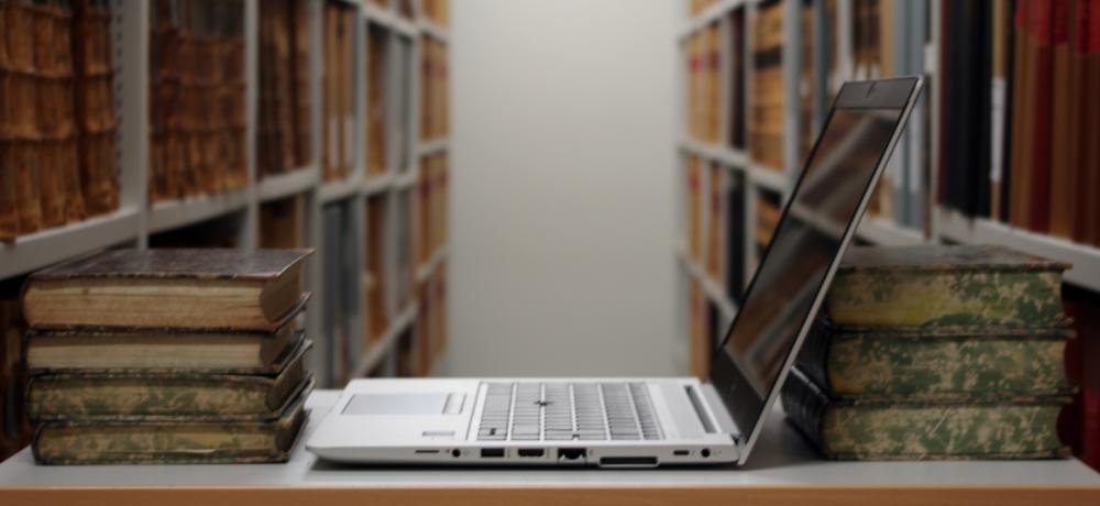 Dator och gamla böcker på ett bord