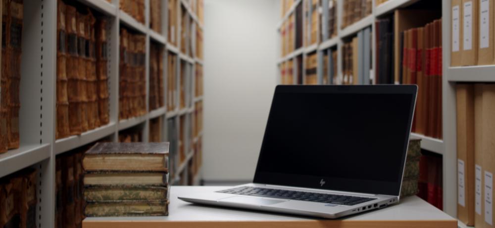 Dator och böcker på ett bord
